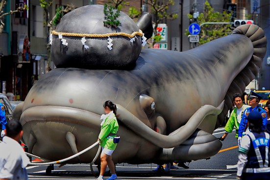 A float in the shape of a giant catfish with a large stone placed on its head is drawn by festival goers during the annual Kanda  Myojin Festival parade in Tokyo Sunday, May 9, 2010. The fish is locally known as the symbol of earthquakes and the sacred keystone is believed to contain the power of temblors.(AP Photo/Itsuo Inouye)